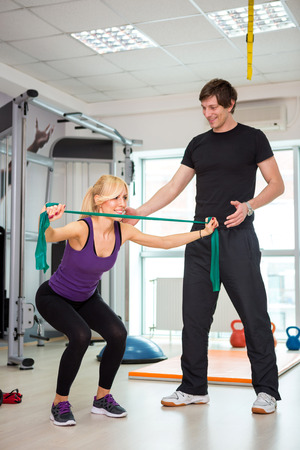 personal trainer man coach and woman exercising with rubber bands photo