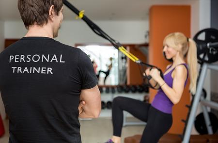 パーソナル トレーナーは、彼の背中は、カメラに直面するいると彼のクライアントを見て