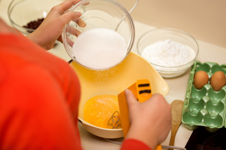 mixing raw eggs in bowl and add sugar photo