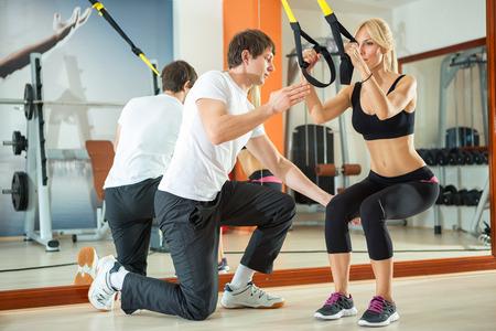 Vrouw training met fitness bandjes onder begeleiding van een personal trainer