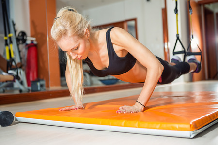 fit woman in fitness salon in push up pose exercise Stock Photo