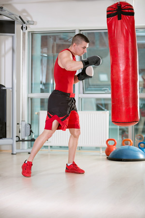 Young man practicing kicks with a punching bag at a gym photo