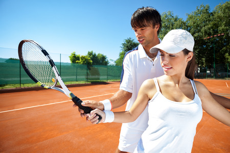sport leisure:  Woman and male tennis instructor practicing racket control on tennis court Stock Photo