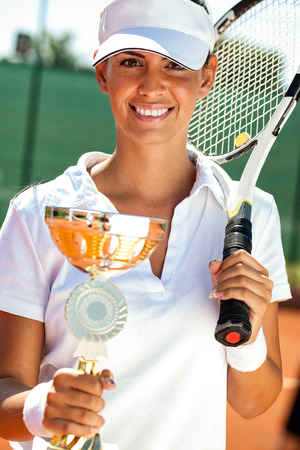 young female tennis player showing golden goblet photo