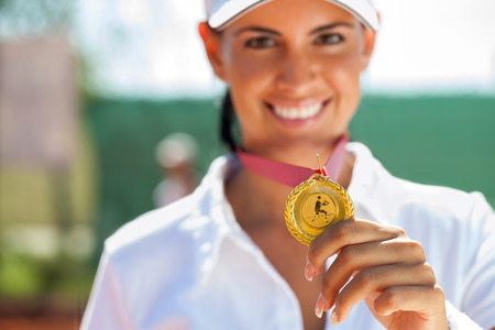 successes:  Winner female tennis player with a golden medal