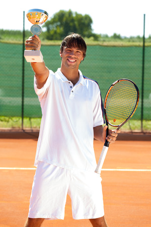 Smiling tennis winner showing his golden  goblet photo