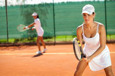 테니스 코트에서 테니스에서 복식을 재생하는 젊은 여성 스톡 콘텐츠