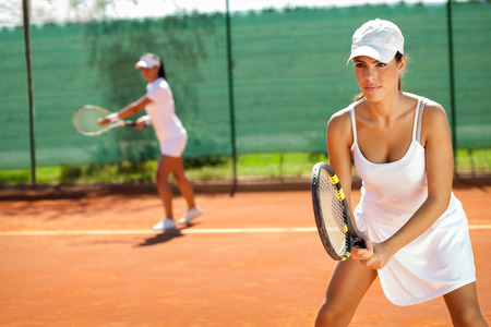young women playing doubles at tennis at the tennis court photo