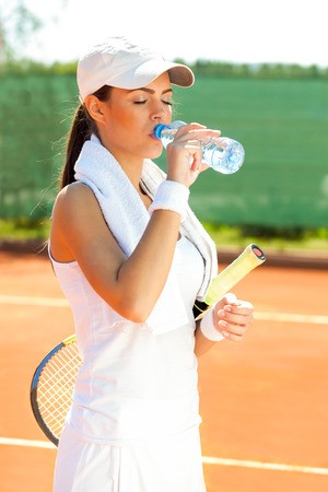 girl drinking water:  Sporty woman with plastic bottle of water after tennis training Stock Photo