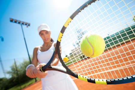 young sporty female tennis player hitting the ball photo