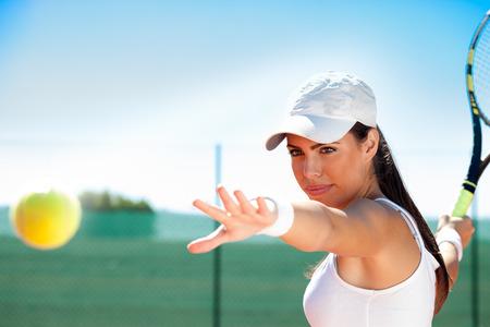 jugando tenis: joven jugador de tenis femenino listo para golpear la bola