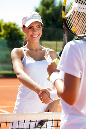 Two women  handshaking at the tennis court after a match photo
