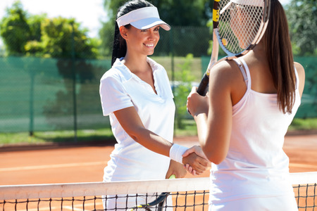 Two female tennis players shaking hand over tennis court  photo
