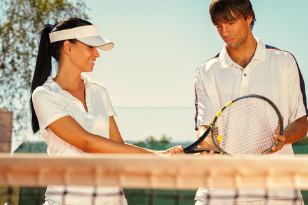 Young couple of tennis players talking photo