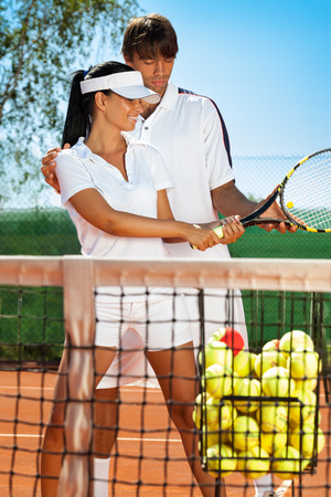 young sportswoman with instructor practicing tennis  photo