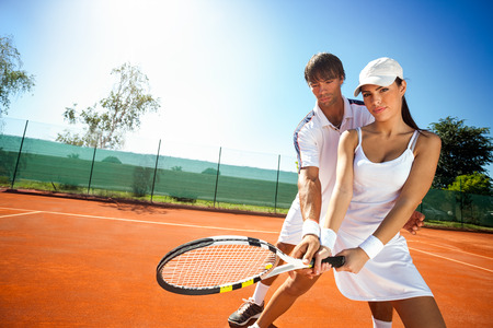 Young female sporty girl and her coach during practice tennis photo
