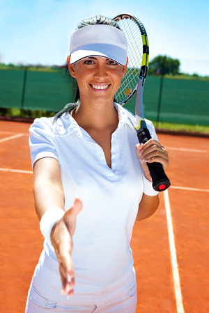 smiling female tennis player giving hand for handshake, fair player photo