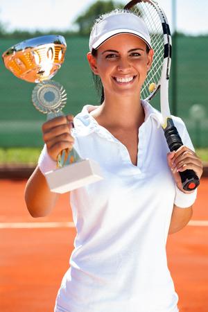 successes: giovane giocatore di tennis ragazza che mostra calice d'oro Archivio Fotografico