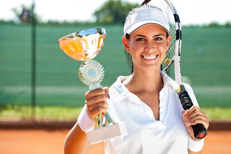 successes:  Female tennis player won the cup at the sport competition, prize and victory