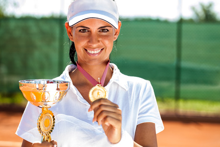 Tennis player won the cup at the sport contest, trophy photo