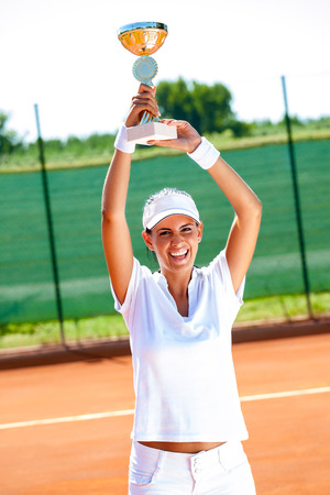 successes: Pretty tennis player won the cup at the sport competition, victory Stock Photo