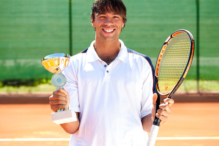 successes: Young happiness tennis player won the cup, trophy