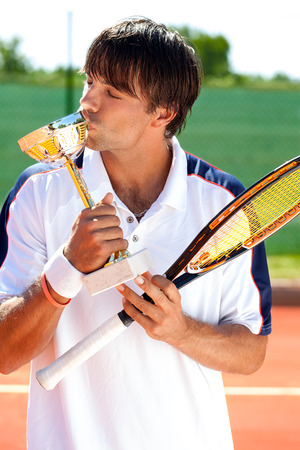 glad sporty man kissing trophy, victory at sport competition photo