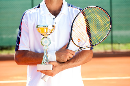 successes:  tennis player with golden  goblet