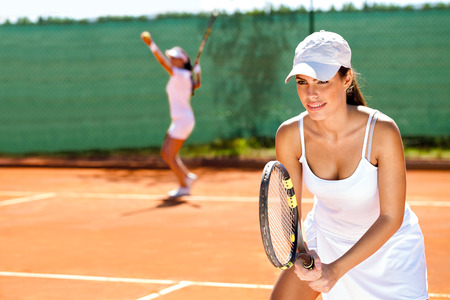 two tennis player playing doubles at tennis court photo