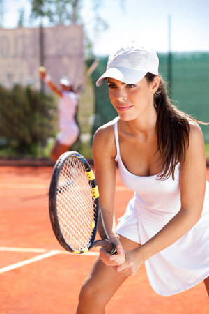 Woman holding a tennis racquet at the tennis court photo