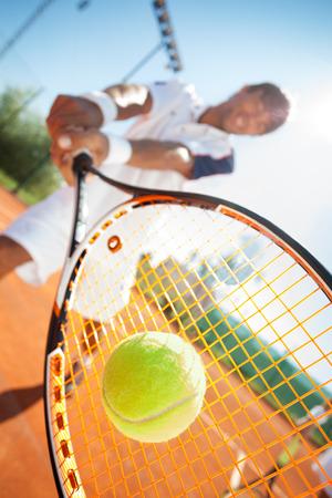 tennis racket: hombre jugador de tenis que golpea la bola con la raqueta Foto de archivo