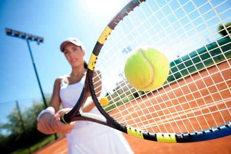 jugando tenis: mujer joven que juega a tenis en un día soleado