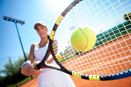 in action: young woman playing tennis on a sunny day Stock Photo