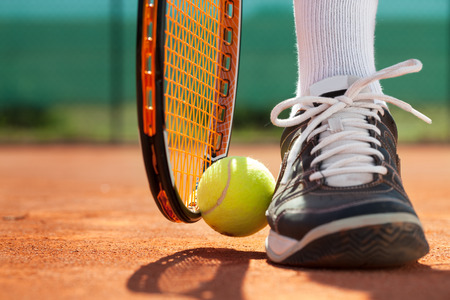 raqueta de tenis: Piernas de hombre deportivo cerca de la raqueta de tenis y bolas