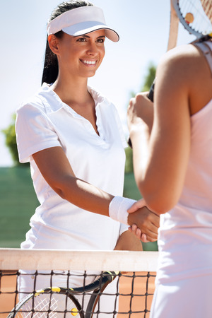 Women handshaking after playing a tennis match photo