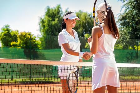 jugando tenis: Mujeres apretón de manos después de jugar un partido de tenis Foto de archivo
