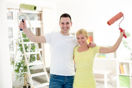 Happy couple holding raised paint roller, concept painting apartment photo