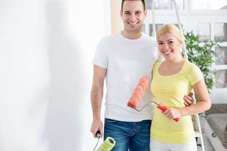 Young couple painting wall in the apartment photo