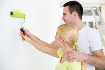 Affectionate  young couple painting wall together photo