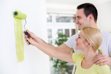 young couple painting wall together with  paint roller  photo