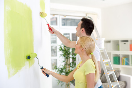 Affectionate couple painting together a room in their new house