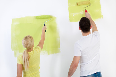 Young couple painting wall at home in green, back view photo