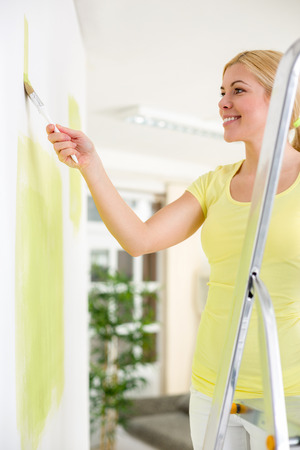 Woman standing on a ladder and painting a white wall with a vibrant yellow paint using a roller as she redecorates her house  photo