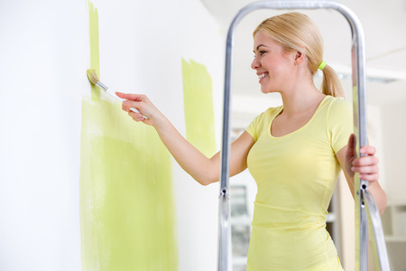 Smiling young woman painting wall in her new home while standing on ladder photo