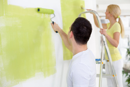 Couple in their new home painting wall in green  photo