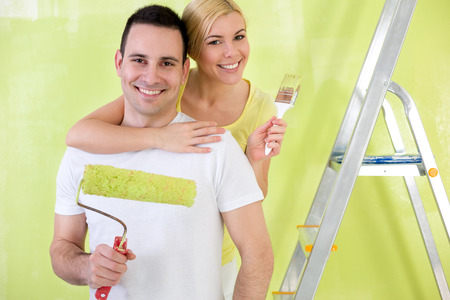 Portrait of smiling Lovers with paint brush painting photo