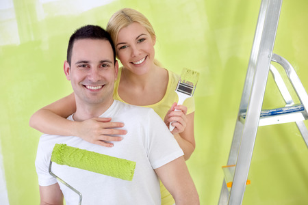 Young affectionate,  happy handy couple painting new house photo