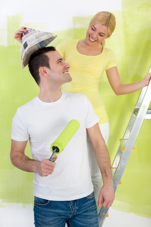 Happy  couple painting, woman put the paper hat on boyfriends head  photo