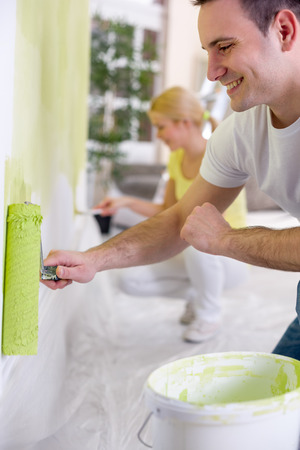 Smiling couple painting wall in green  photo