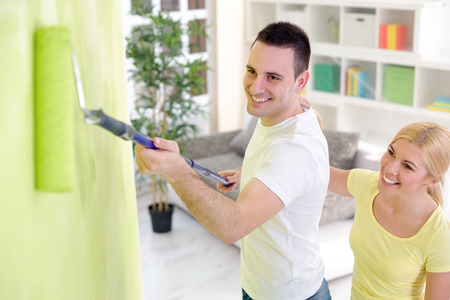 Young cheerful couple painting their home, concept renovation photo